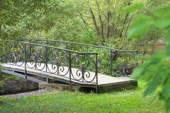 Kleine empfindliche hölzerne Bogenbrücke über einem ruhigen Strom tief im alten, starken Ferienpark Stockfoto