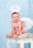 Kleine en gelukkige engel die en op een stoel glimlachen zitten Royalty-vrije Stock Foto's