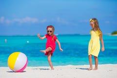 Kleine entzückende Mädchen, die mit Ball auf dem Strand spielen Lizenzfreies Stockfoto