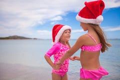 Kleine entzückende Mädchen in Sankt-Hüten während des Strandes Stockfotografie