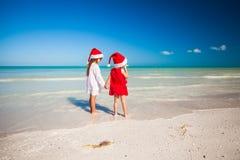 Kleine entzückende Mädchen in Sankt-Hüten während des Strandes Stockfotos