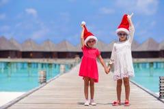 Kleine entzückende Mädchen in Sankt-Hüten während des Strandes Stockbilder