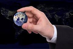 Kleine Erde in einer Hand Stockbilder