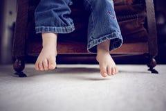Kleine Füße, die über einem Stuhl baumeln lizenzfreie stockfotos