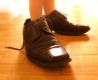 Kleine Füße in den großen Schuhen Lizenzfreie Stockbilder