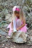 Kleine feenhafte Ballerina, die auf einem Stein in einem Wald sitzt Stockfotografie