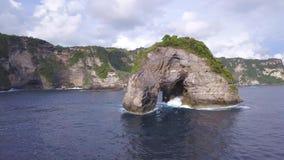 Kleine Felsen-Bogen-Insel im Meer Nusa Penida, Indonesien 4K fliegen um Vogelperspektive stock video footage