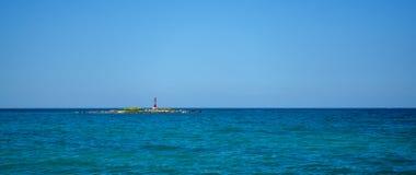 Kleine Felseninsel mit einem Leuchtturm im Mittelmeer Stockbild