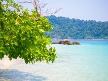 Kleine Felseninsel mit undeutlichem Baumastvordergrund Lizenzfreie Stockfotografie