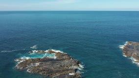Kleine felsige kleine Insel der oberen Ansicht gewaschen durch enormen Anspornungsozean stock footage
