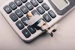 Kleine Figürchen des Mannmodells eingewickelt in den Verbänden auf Taschenrechner stockfoto