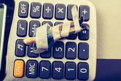 Kleine Figürchen des Mannmodells eingewickelt in den Verbänden auf Taschenrechner stockfotografie