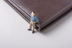 Kleine Figürchen des Mannmodells neben einer Geldbörse lizenzfreies stockbild