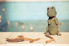 Kleine Figürchen eines netten Krokodils am Rand eines leeren Swimmingpools Getrennt auf Weiß Stockbild