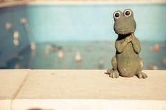Kleine Figürchen eines netten Krokodils am Rand eines leeren Swimmingpools Getrennt auf Weiß Lizenzfreie Stockfotografie
