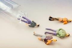 Kleine Figürchen von Männern modellieren das entgehen der Flasche stockfotografie