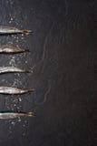 Kleine Fische mit Salz auf dem Tisch Stockfotos