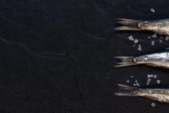 Kleine Fische mit Salz auf dem Tisch Lizenzfreies Stockbild