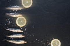 Kleine Fische mit Zitrone auf dem Tisch Lizenzfreie Stockfotografie