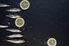 Kleine Fische mit Zitrone auf dem Tisch Stockbilder