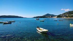 Kleine Fischerboote auf dem azurblauen Wasser in der Mitte von Budva, in Montenegro Stockfoto