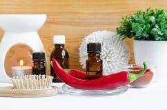 Kleine Flasche mit Pfeffer-Auszugtinktur des roten Paprikas, Infusion, Öl, frischer Paprikapfefferhülse und hölzerner Haarbürste stockfotos