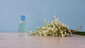 Kleine Flasche Parfüm und Blumenstrauß von Maiglöckchenblumen auf helle Farbhintergrund Parfümerie, Duft, Kosmetik lizenzfreie stockfotos