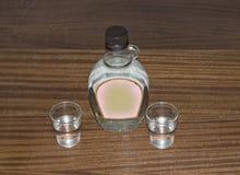 Kleine Flasche Wodka und zwei Gläser Stockbild
