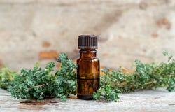 Kleine fles essentiële thymeolie op de oude houten achtergrond Aromatherapy, kuuroord en kruidengeneeskundeingrediënten royalty-vrije stock afbeeldingen