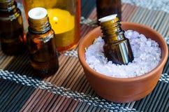 Kleine fles etherische olie in de kom met het zout van het aromabad Aromatherapy, kuuroord en kruidengeneeskundeconcept royalty-vrije stock foto