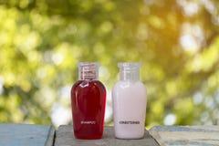 Kleine fles van shampoo en veredelingsmiddel met abstract aard bokeh onduidelijk beeld Stock Afbeelding