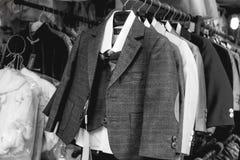 Kleine gantleman Klagen, die an einem Kleiderbügel hängen lizenzfreies stockbild