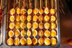 Kleine gegrillte Omelette auf den Stöcken Chinesisches traditionelles stree stockbild