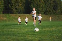 Kleine gelukkige kinderen op voetbalgebied stock fotografie