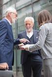 Kleine gemischte Gruppe Geschäftsleute, die eine Sitzung, Verkaufsberichte besprechend haben stockfoto