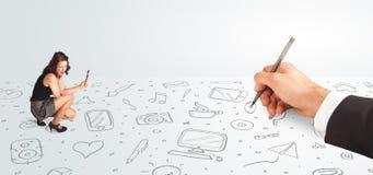 Kleine Geschäftsfrau, die gezeichnete Ikonen und Symbole zur Hand schaut Stockfotografie