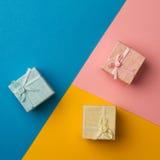 Kleine Geschenkboxen auf mehrfarbigem Papierhintergrund Lizenzfreie Stockfotografie