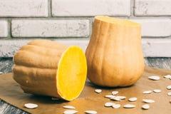 Kleine gesneden pompoenen met zaden op keukenlijst Stock Foto's