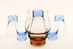 Kleine Gläser und ein großes Glas. Lizenzfreies Stockfoto