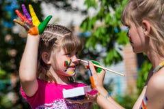 Kleine glückliche Schwestern spielen mit Farben im Park, Kinderspiel, Kinderfarbe Stockfotos