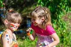 Kleine glückliche Schwestern spielen mit Farben im Park, Kinderspiel, Kinderfarbe Lizenzfreies Stockfoto