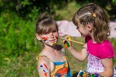 Kleine glückliche Schwestern spielen mit Farben im Park, Kinderspiel, Kinderfarbe Lizenzfreies Stockbild