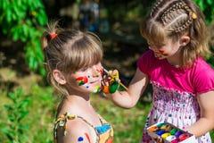 Kleine glückliche Schwestern spielen mit Farben im Park, Kinderspiel, Kinderfarbe Lizenzfreie Stockbilder