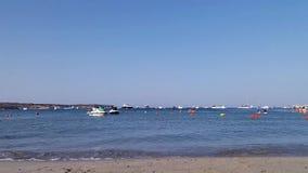 Kleine golven op het zandige strand in Mellieha, Malta, waterautopedden en boten, en unrecognisable mensen in het overzees stock videobeelden
