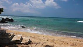 Kleine golven van duidelijk tropisch water die zandig strand voor cementstappen raken stock videobeelden