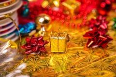 Kleine gouden gift-doos dichtbij rode parel en boog Stock Foto