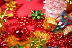 Kleine gouden giftdoos dichtbij rode parel en boog Royalty-vrije Stock Afbeeldingen