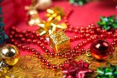 Kleine gouden giftdoos dichtbij rood parel en boogclose-up Stock Foto