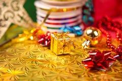 Kleine gouden giftdoos dichtbij rood parel en boogclose-up Stock Foto's