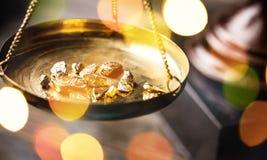 Kleine gouden goudklompjes in een antieke het meten schaal stock fotografie